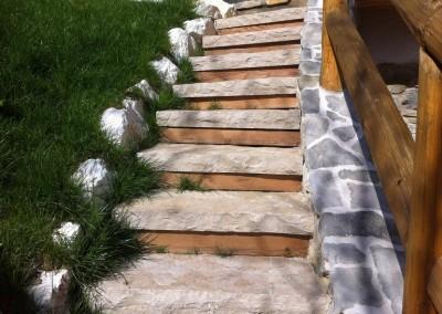 Scalinata con posa di pietre e alzate in legno di larice (lavori di finitura)